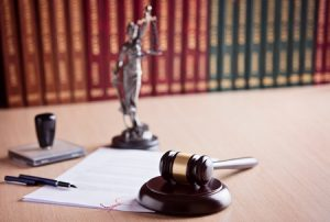 53483537 - court judge's gavel, themis - the goddess of justice and law codes in the background. law office. law concept.